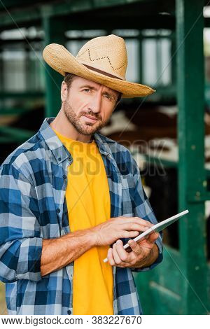 Rancher In Straw Hat And Checkered Shirt Using Digital Tablet While Looking At Camera