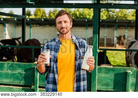 Rancher In Plaid Shirt Looking At Camera While Holding Bottle And Glass Of Fresh Milk On Farm