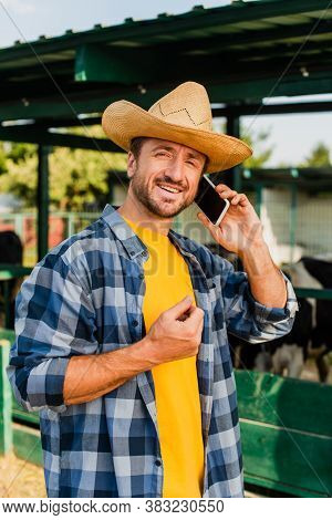 Rancher In Straw Hat And Plaid Shirt Talking On Smartphone Near Cowshed