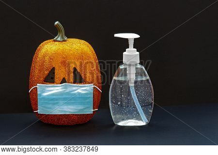 Jack-o-lantern Pumpkin Halloween Wearing A Face Mask With Hand Sanitizer Bottle On A Black Backgroun