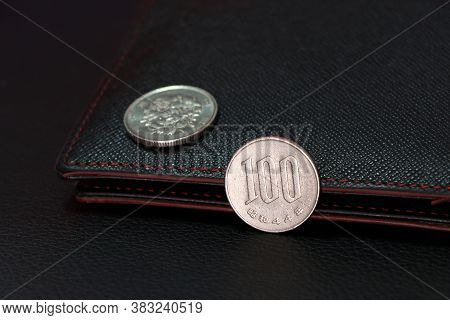 Japanese One Hundred Yen Coins On Reverse (jpy) And Out Focus Hundred Yen On Obverse With Black Wall