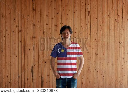 Man Wearing Malaysia Flag Color Shirt And Standing With Two Hands In Pant Pockets On The Wooden Wall