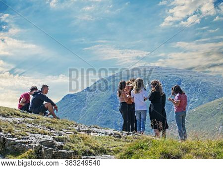Group Of Young People Traveling In The Mountains. Beautiful Mountain Scenery. Romania, Transalpina.