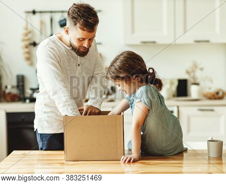 Young Man And Little Daughter Unpacking Carton Box With Delivered Order While Spending Time Together