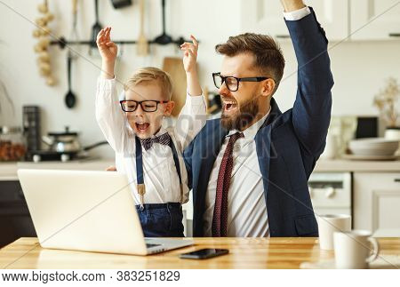 Young Male Entrepreneur In Formal Clothes And Eyeglasses With Little Son In Formal Wear Looking At L