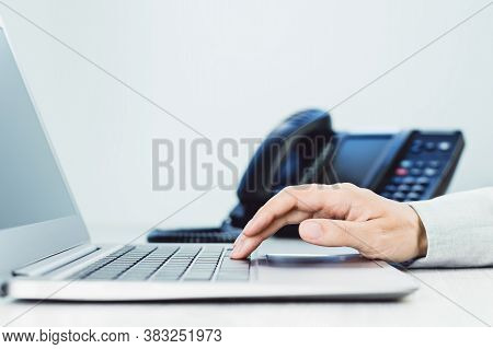 Business And Communications. Female Hand And Voip Phone In The Office. Finance Graphs. Laptop On Des