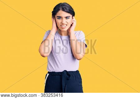 Brunette teenager girl wearing casual clothes covering ears with fingers with annoyed expression for the noise of loud music. deaf concept.