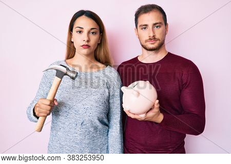 Beautiful couple holding piggy bank and hammer thinking attitude and sober expression looking self confident