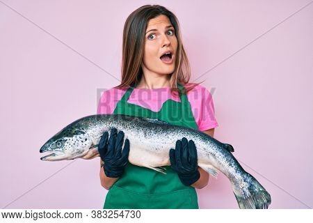 Beautiful caucasian woman fishmonger selling fresh raw salmon in shock face, looking skeptical and sarcastic, surprised with open mouth