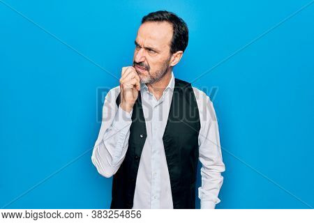 Middle age handsome man wearing elegant shirt and vest over isolated blue background thinking concentrated about doubt with finger on chin and looking up wondering