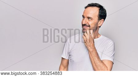 Middle age handsome man wearing casual t-shirt standing over isolated white background thinking concentrated about doubt with finger on chin and looking up wondering