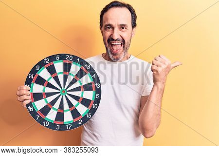 Middle age handsome man holding dartboard standing over isolated yellow background pointing thumb up to the side smiling happy with open mouth