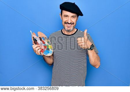 Middle age handsome artist man wearing french beret drawing using paintbrush and palette smiling happy and positive, thumb up doing excellent and approval sign