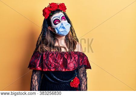 Young woman wearing day of the dead costume wearing medical mask looking away to side with smile on face, natural expression. laughing confident.