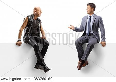 Punk talking with to a young man in a suit and tie while sitting on a panel isolated on white background