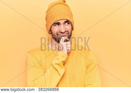 Young handsome bald man wearing sweater and wool cap thinking concentrated about doubt with finger on chin and looking up wondering