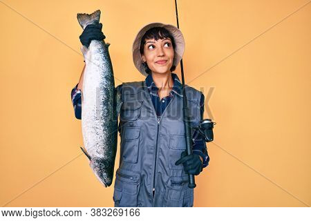 Beautiful brunettte fisher woman holding fishing rod and raw salmon smiling looking to the side and staring away thinking.