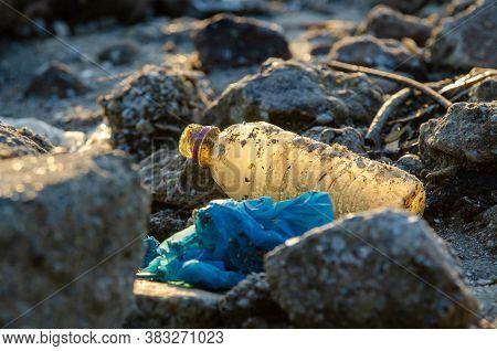 Plastic Bottle At Rock. Plastic Contamination. Environmental Pollution.
