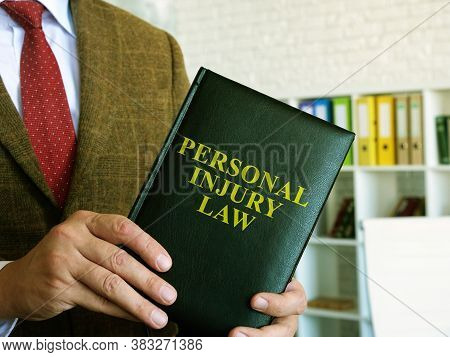 Personal Injury Law. A Lawyer In A Suit Holds A Book.