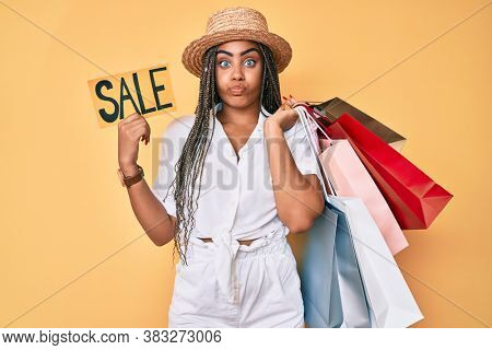 Young african american woman with braids holding shopping bags and sale banner puffing cheeks with funny face. mouth inflated with air, catching air.
