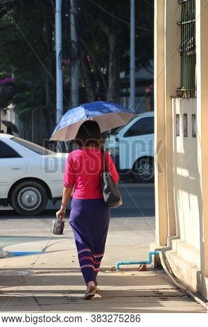 Backside Of Myanmese Woman Walking On The Walkway Beside The Street On The Morning.