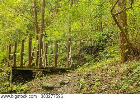 Small Wooden Footbridge Over Ravine In Mountainside Wilderness Park.
