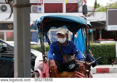 Pathumthani, Thailand - 29 May, 2020 : The Man Who Rides The Tricycle Hire Wearing Hygienic Mask Sit