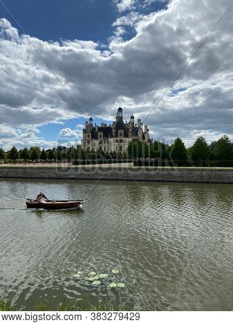 Chambord, France,  August 23, 2020 - Two people in a small boat on the water in front of Chateau de Chambord in the Loire Valley, UNESCO world heritage in France