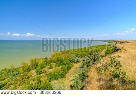 View Of The Sea From A High Clay Bank On A Sunny Summer Day Against The Backdrop Of A Cloudless Blue