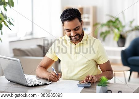 remote job, technology and people concept - young indian man with calculator and papers working at home office