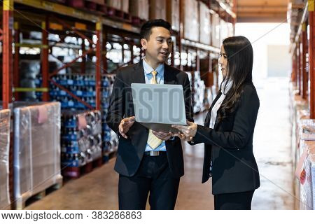 Portrait of businessman discuss with businesswoman wit computer laptop about inventory with factory large distribution warehouse. Business investment merger acquisitions concept.
