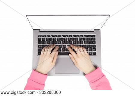 Person Working On A Laptop Computer In A Modern Space. Female Hands In Pink Hoodie Working On New La