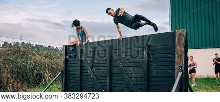Group Of Participants In An Obstacle Course Climbing A Wall