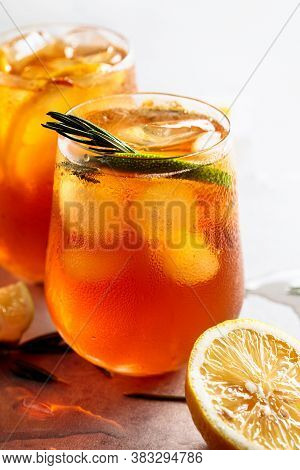 Iced Tea With Lemon, Lime And Ice Garnished With Rosemary. Frozen Glasses With Citrus Slices.