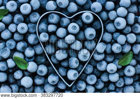 Background Of Fresh Frozen Blueberries With A Metal Heart Shape. Texture Of Blueberries Close-up.