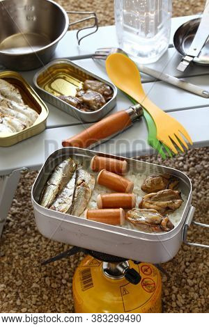 camping cooking. oiled sardines, sausages and smoked oysters on boiled rice in mess tin.