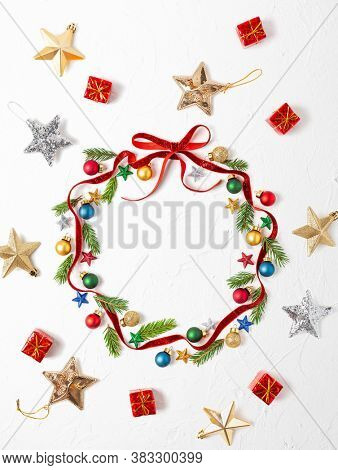 Christmas composition  with red ribbon ,branches of fir tree and Christmas ornaments in shape of Christmas bauble on white background. Merry christmas greeting card with empty space for holiday text.