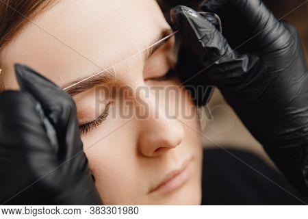 Master Applies Thread To Woman On Brow. Correction And Tinting Eyebrows