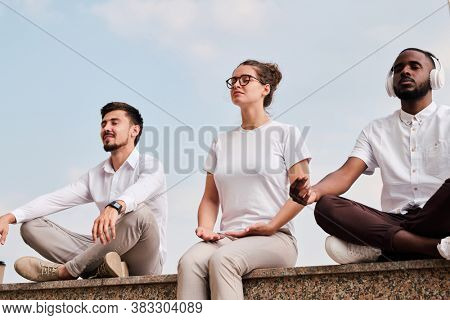 Group of young multi-ethnic people sitting in relaxed position and meditating to concentrate on thoughts outdoors