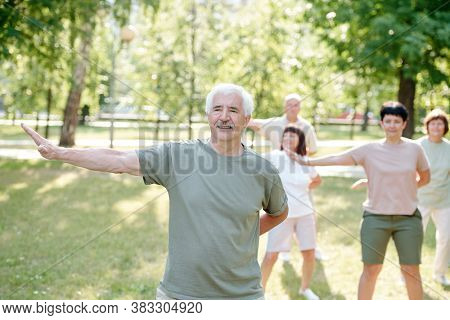 Handsome senior man with mustache practicing qigong exercise to be healthy and calm at group class in park