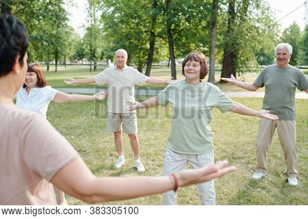 Rear view of qigong instructor keeping arms outstretched while teaching senior people to breathe deeply