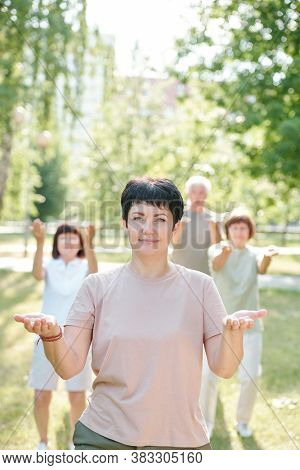 Portrait of smiling qigong teacher showing palms against her students in summer park