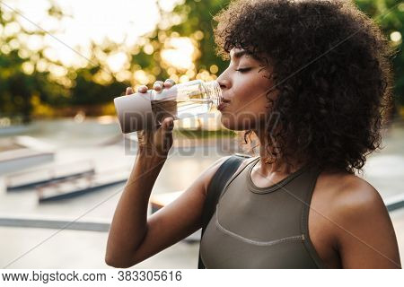 Image of african american sportswoman drinking water while working out on sports ground