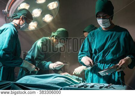 Operating room nurse prepare surgical equipment for surgeon doctor with Medical Team Performing Surgical Operation in Operating Room OR. Medical health care Surgery concept.