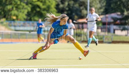 Young Field Hockey Female Player Hitting The Ball
