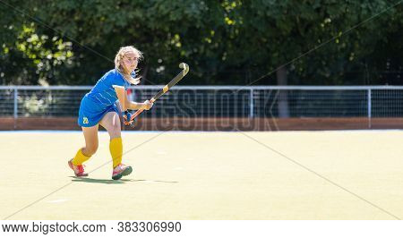 Young Field Hockey Female Player On The Pitch