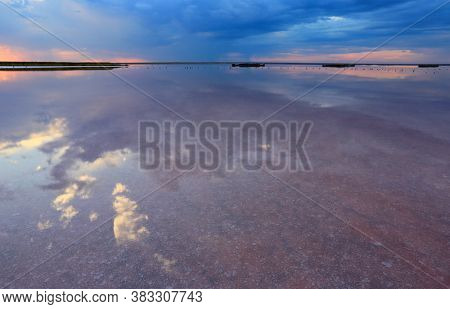 evening landscape with nice clouds over dead salt lake water surface, take it ib Azov Sea in Ukraine.  Reflection of the evening sky in the surface of a salt lake