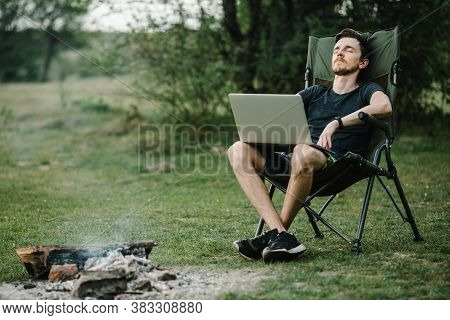 Young Freelancer Relaxing In Forest. Man Working On Laptop On Nature. Remote Work, Outdoor Activity