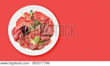 Marbled beef carpaccio with arugula, spices and parmesan cheese. Top view flat lay with copy space