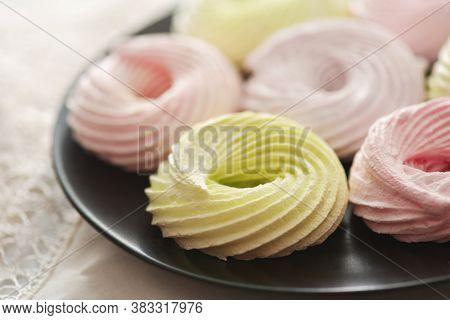 Close up of fresh meringue rings on black plate